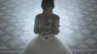 Slow motion shot of a beautiful bride in white wedding dress with bridal bouquet looking at the camera