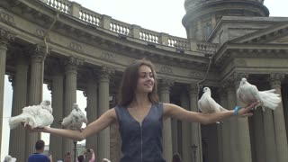 Slow motion shot of a beautiful girl releasing a white pigeons from her arms with Cathedral on the background