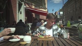 Slow motion shot of a boy looks at a glass in an outdoor cafe, water flowing up from the glass