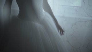 Slow motion shot of a bride hand on white dress,ready for marriage ceremony