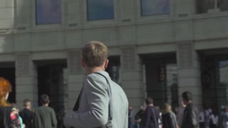Slow motion shot of a confused man looking for someone in the city square