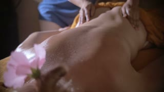 Slow motion shot of a female back being massaged with hot stones.