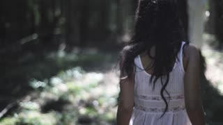 Slow motion shot of a frightened young woman in white dress walk in the woods
