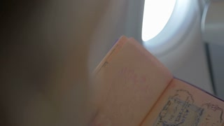 Slow motion shot of a hand turning pages of a travel passport with marks of entrance to different countries. Person is sitting in the plane.