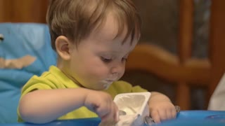 Slow motion shot of a little boy in high chair finished eating food with spoon.