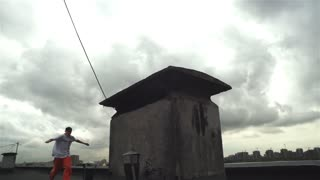 Slow motion shot of a male young roofrunner jumping on the roof