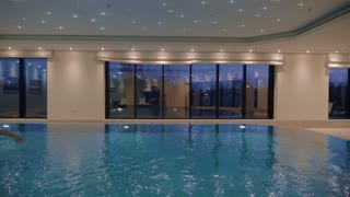 Slow motion shot of a man swimming freestyle in indoor swimming pool.