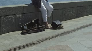 Slow motion shot of a street female violinist plays at seafront with sea on the background