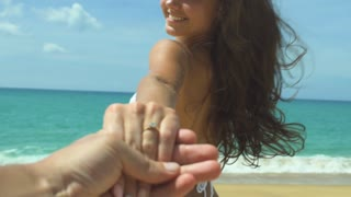 Slow motion shot of a woman wanting her man to follow her in vacation or honeymoon to beach by the ocean