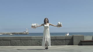Slow motion shot of a young happy girl releasing a white pigeons on seaside promenade