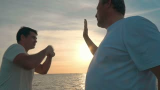 Slow motion shot of a young man trying to punch his father's hand jokingly.