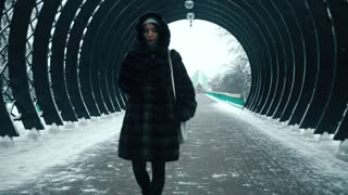 Slow motion shot of beautiful young woman in fur coat walking through outdoor park gallery