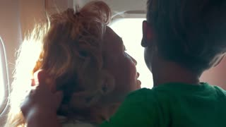 Slow motion shot of mature woman and little boy looking out the plane window. They are turned backs to the camera.