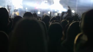Slow motion shot of people standing in front of the stage and watching the show of a musical band.