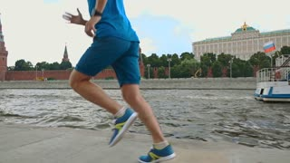 Slow motion steadicam shot of athletic man runner against Moscow Kremlin 120 fps