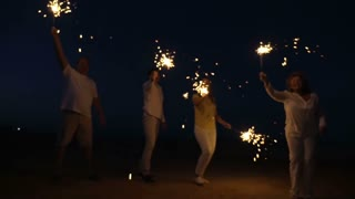 Slow motion steadicam shot of friends or family with firework sparklers on the beach at night. Celebration time