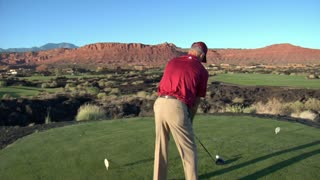 Slow-motion  Steadicam Shot Of Man Teeing Off On Golf Course With Sunset And Red Rock Cliffs