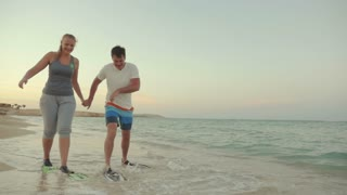 Slow motion steadicam shot of young man and woman walking in flippers along the sea shore. They look funny and clumsy