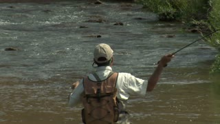 Slow Motion Tight Shot Of Fly Fisherman And Red Rock Cliffs