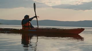 Slow motion tracking of man in life jacket kayaking on lake in pink dusk lighting, misty mountains in distance