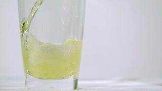 Slow Motion Yellow Soda Filling Glass Closeup