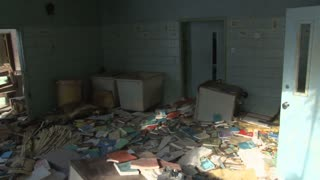 Slow pan across room full of old books, dirt and debris.