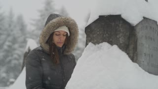 slow pan across woman visiting grave during snowstorm