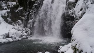 slow pan up a spectacular waterfall covered in snow