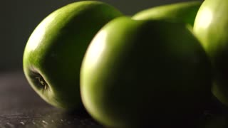 Slow panoramic shot of multiple green apples
