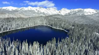 Slowly soaring over snowy Lost Lake in Vail Colorado in winter