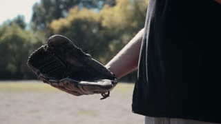 Slowmotion Close Up of Man Wearing Baseball Glove and Tossing Baseball from Hand to Hand During Baseball Game Outdoors in Field on Sunny Day in Summer