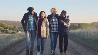 Slowmotion of happy diverse group of four young adult men and women in coats walking on dirt path outside during late afternoon
