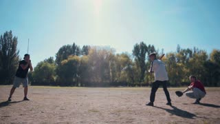 slowmotion Rear View of Male Pitcher Tossing Ball Towards Batter and Catcher in Casual Game of Baseball in Sunny Field on Summer Day