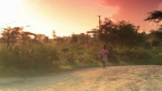 Small Boy Walks Along Dirt Road at Sunrise