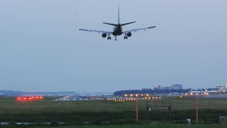 Small Commercial Jet Lands On Distant Tarmac, Early Morning