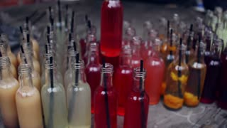 Small liquor bottles. Hand put liquor bottle to other alcohol bottles. Alcoholic drinks in alcohol bar. Red, white, pink, yellow, vinous and beige alcohol in small glass bottles at alcohol store