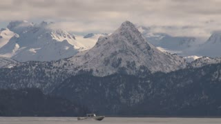 Small Motorboat Passing Snowcapped Mountains