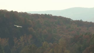 Small Plane Flying Over Hillside