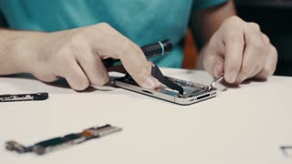 Smart phone repairing with screwdriver and tweezers at service center, close up