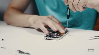 Smart phone repairing with screwdriver at service center, pan