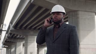 Smiling african man wearing white protective helmet talking on mobile phone while standing under the overpass construction and then looking at camera