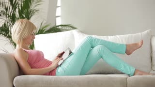 Smiling blonde girl lying on couch with laptop and looking at camera
