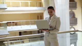 Smiling businesswoman with laptop in the office hall, steadycam shot