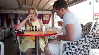 Smiling couple playing a game of chess while sitting at a table enjoying a drink