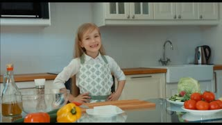 Smiling girl Chef in the kitchen. Child showing vegetables on the table. Thumb up. Ok. Zooming