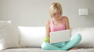 Smiling girl sitting on couch with crossed legs eating apple and using laptop