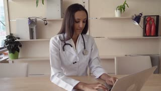 Smiling indian therapist wearing in white lab coat sitting at the wooden table in office. Mixed race professional female work as physician in hospital typing prescription on computer. Multicultural