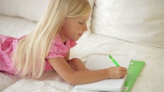Smiling little girl lying on couch and writing in notebook