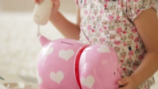 Smiling little girl sitting with pig moneybox on her knees and holding receiver