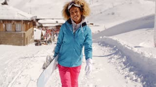 Smiling pretty young woman carrying a snowboard